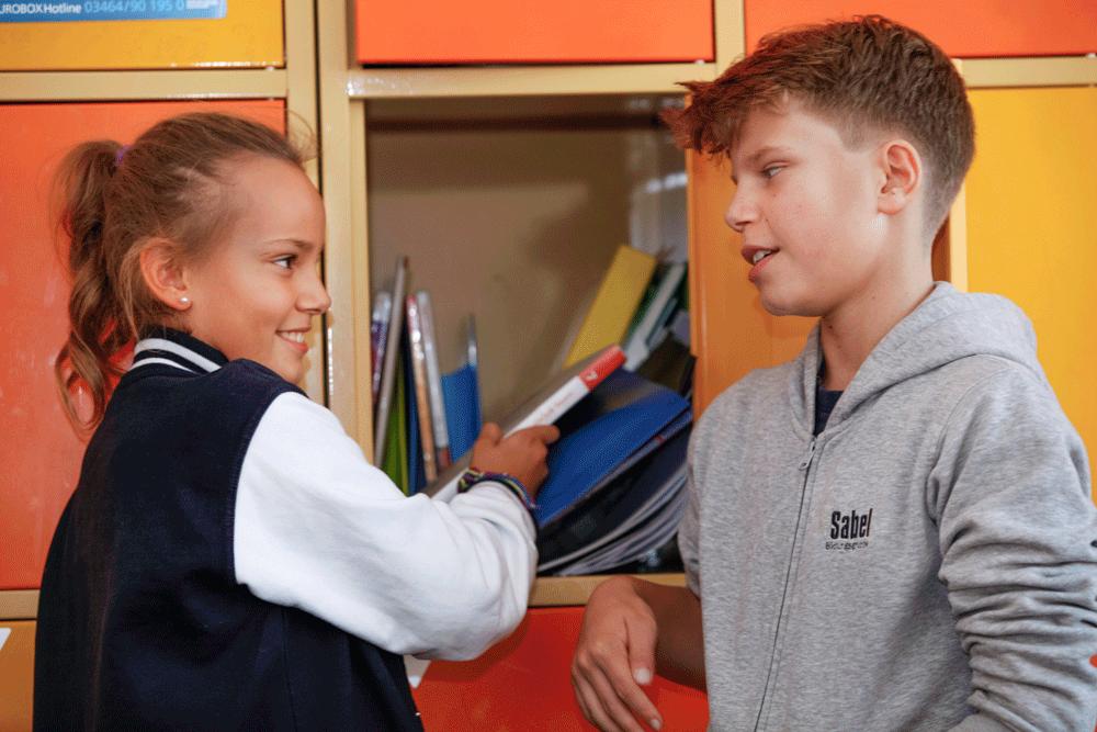 Realschule genehmigt: Eine Schülerin und ein Schüler unterhalten sich