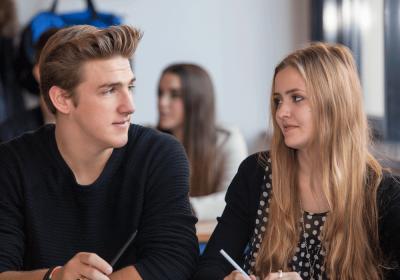 Fachoberschule: Zwei Schüler im Vordergrund in einem Klassenzimmer