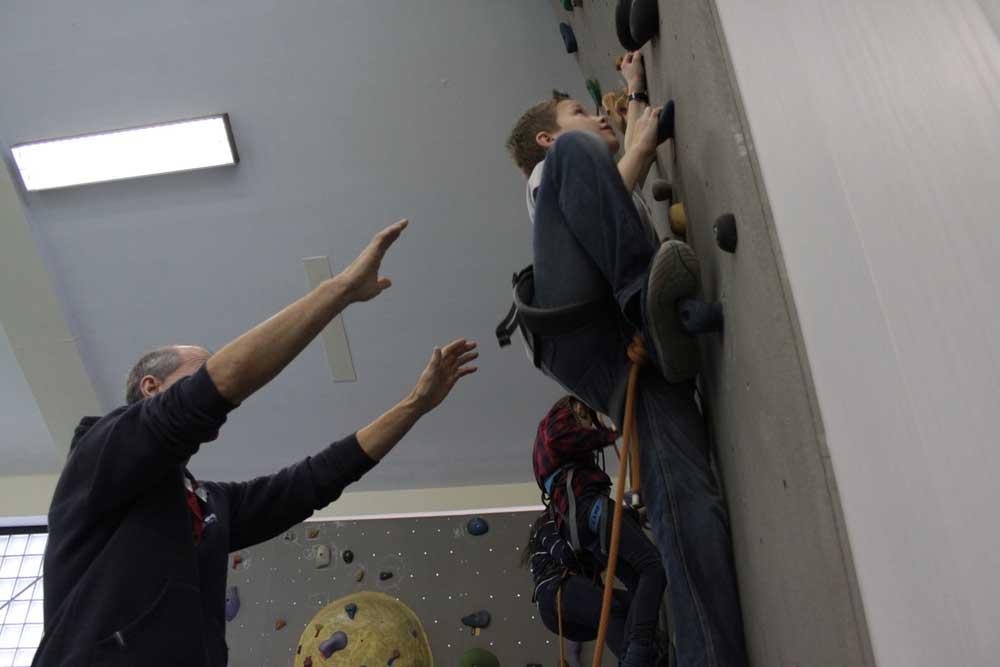 Schüler der SABEL Realschule München wird auf der Boulderwand von einem Kletterlehrer beaufsichtigt