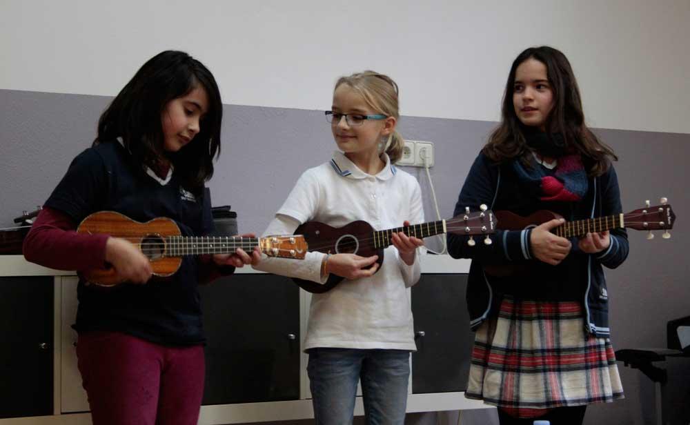 Drei Schülerinnen der SABEL Realschule München spielen Ukulele